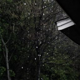 Rain falling from the sky and dripping off a house gutter.